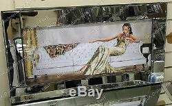 Lady sitting down in cream/gold dress with crystals & mirror frame picture